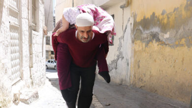 Photo of Şanlıurfa'da yatalak annesini sırtında gezdirdi